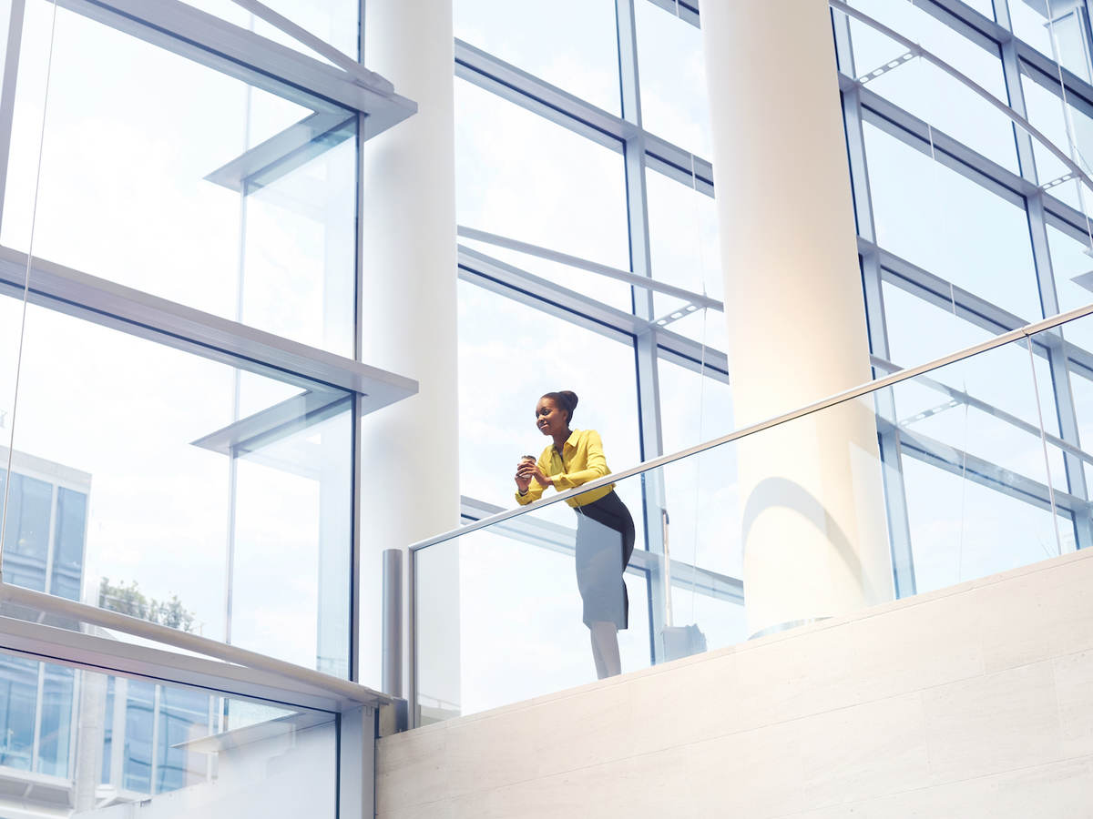 A Black woman looks down from the second floor of an interior office building.