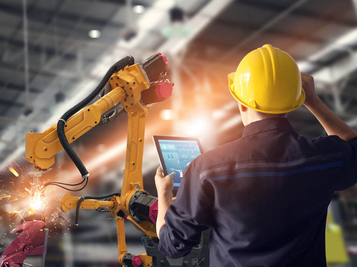 Engineer using a tablet in a factory environment to control a robotic arm