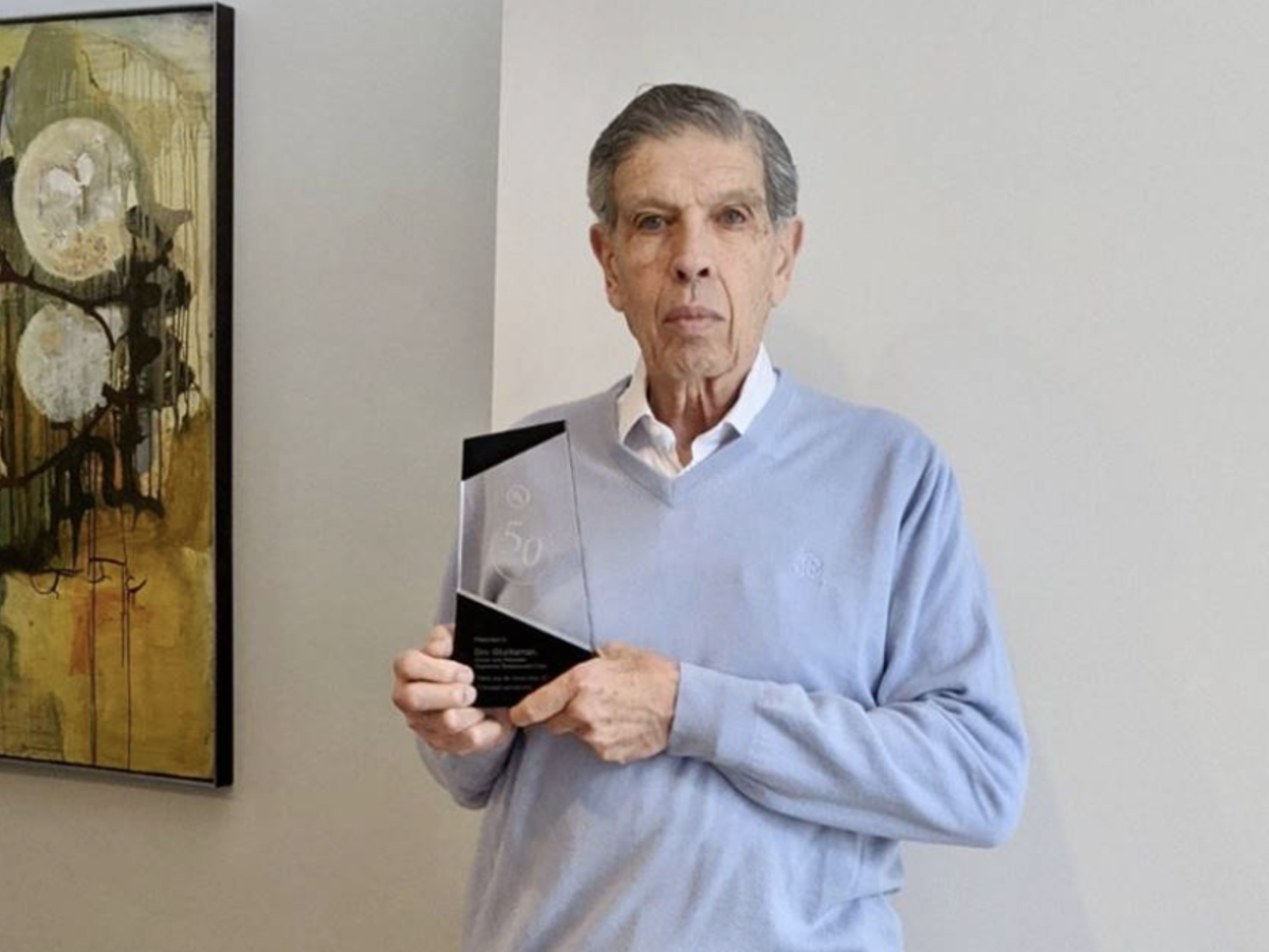 Image of Dov Glucksman holding his commemorative award for 50-years of loyalty.