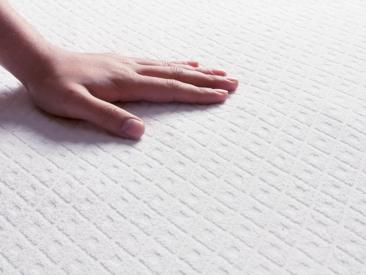 Human hand touching a mattress top