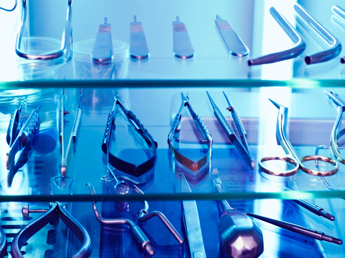 Medical tools sit on a shelf under the blue glow of ultraviolet light, used as a germicidal disinfectant.
