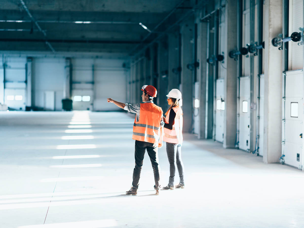 Two people in a warehouse wearing construction hats and vests pointing and looking at something