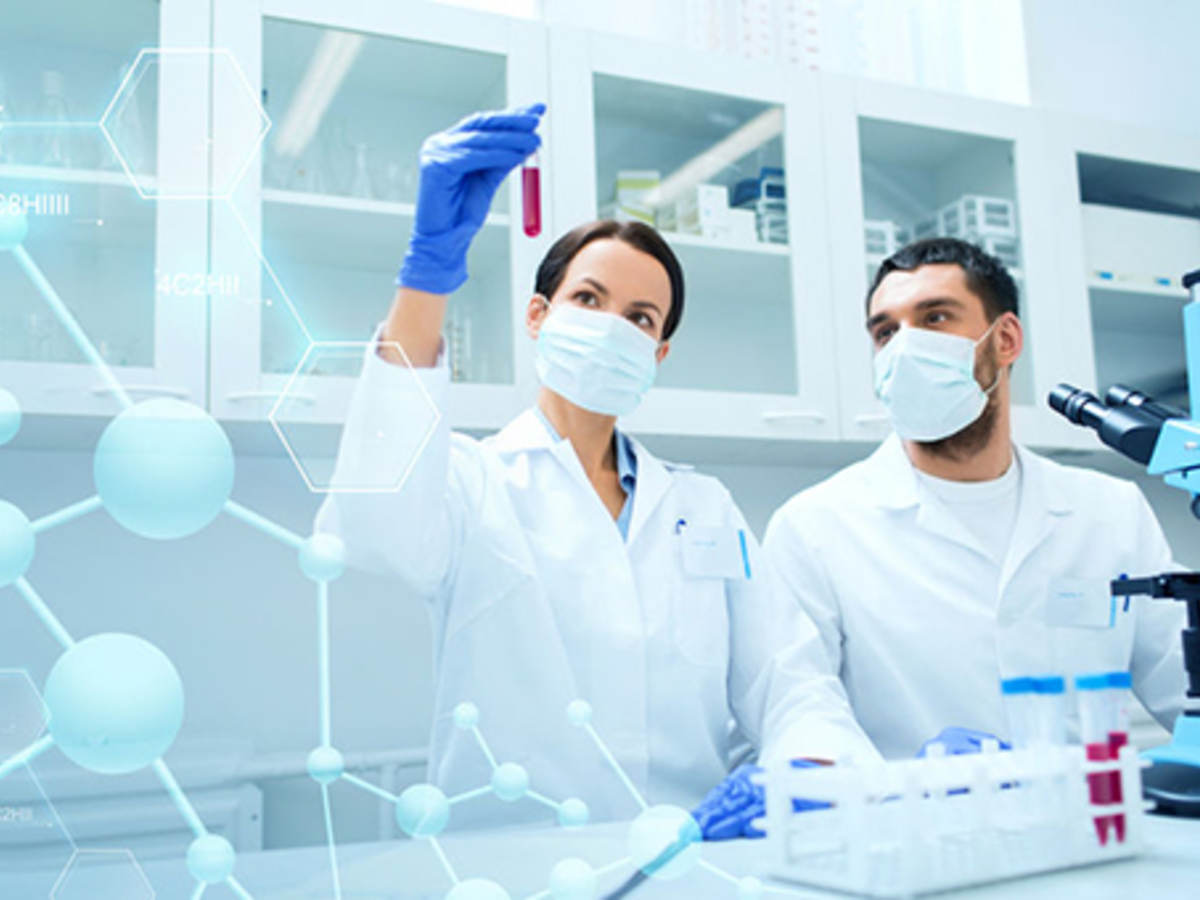 Lab workers looking at red vial