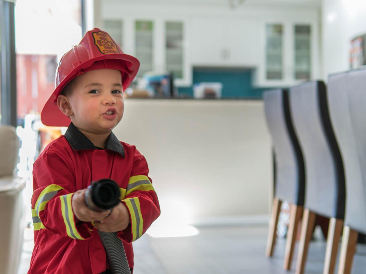 Child dressed like a fireman holding a hose