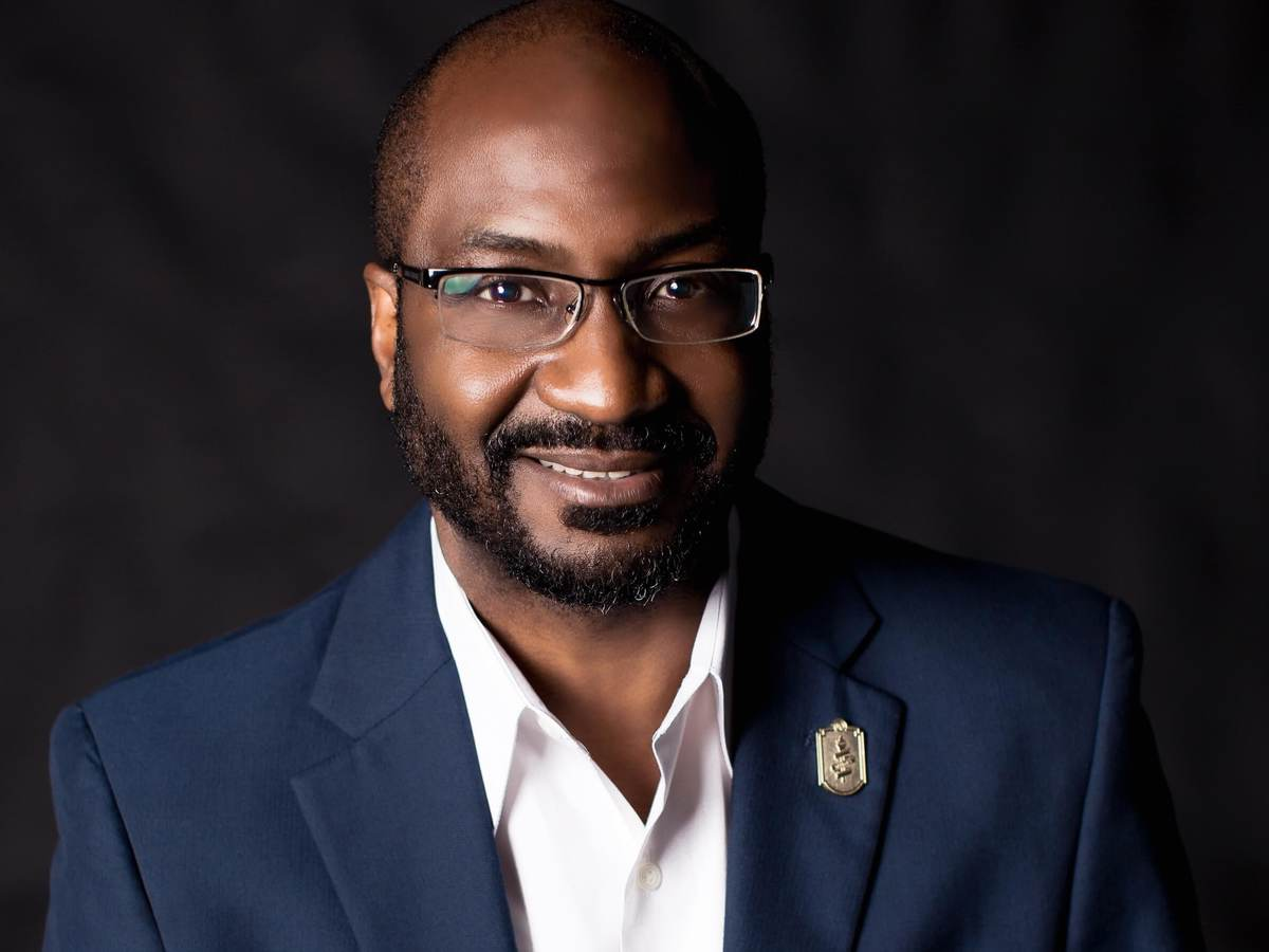 Dwayne Sloan poses for headshot wearing a navy blue jacket, white collar, unbuttoned shirt on a dark background.