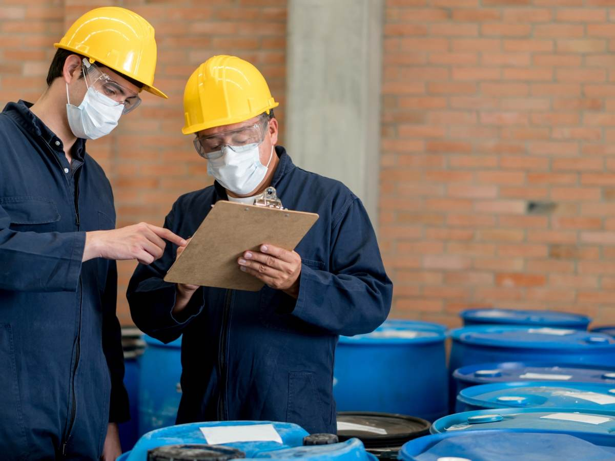 Men in PPE working in chemical warehouse