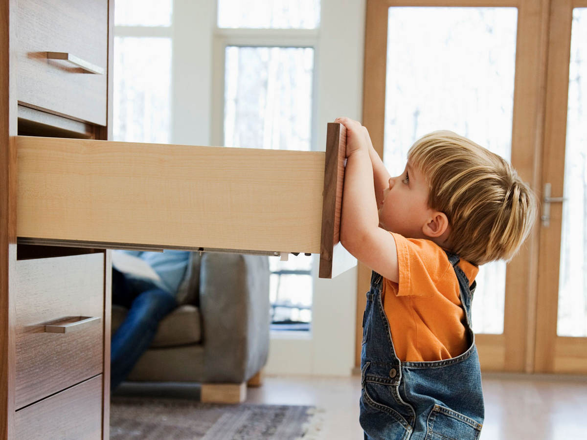 A child pulling on an open dresser drawer, a furniture tip-over risk