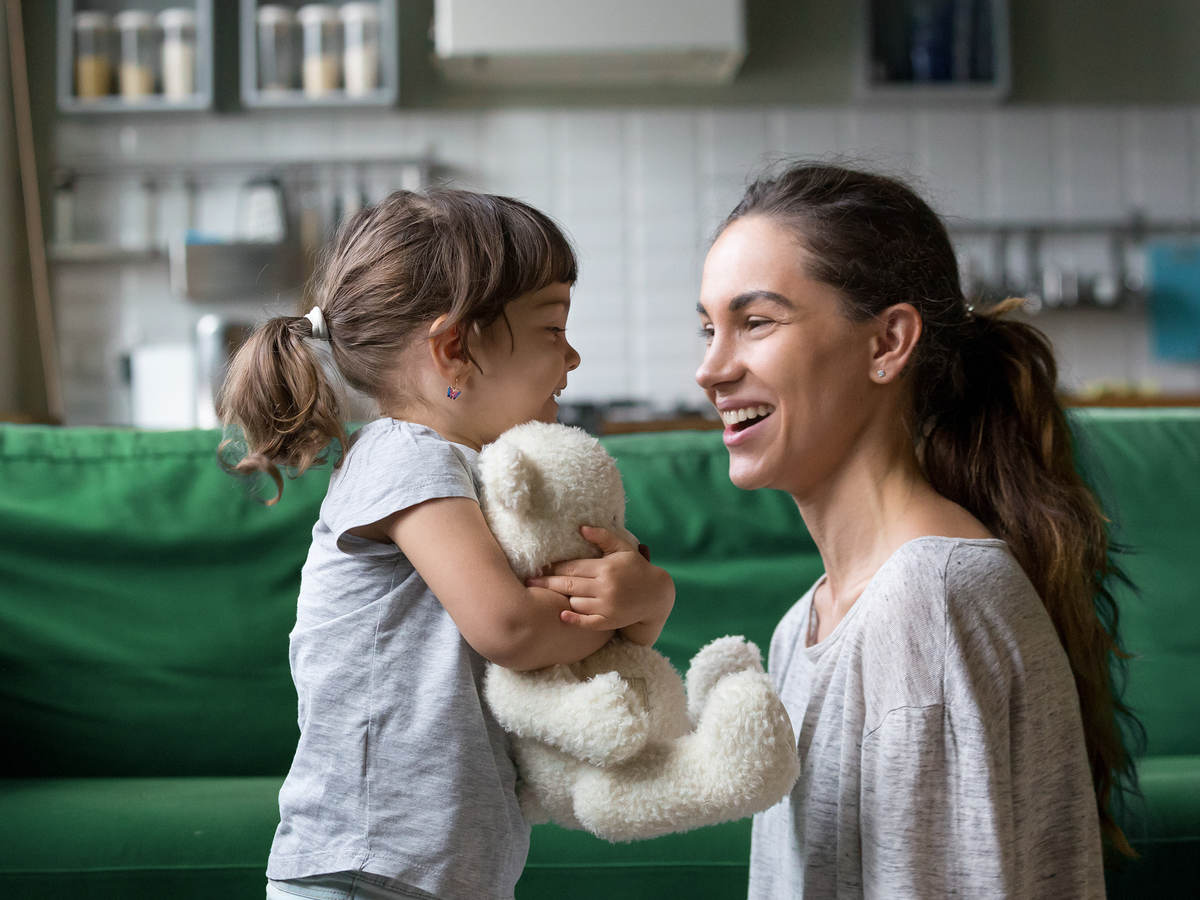 A mother plays in the living room with her child