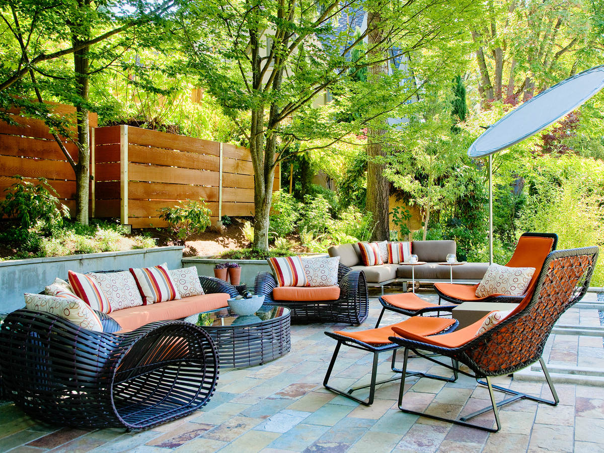 Outdoor furniture including sofa, chairs, table and umbrella in a sunny patio setting