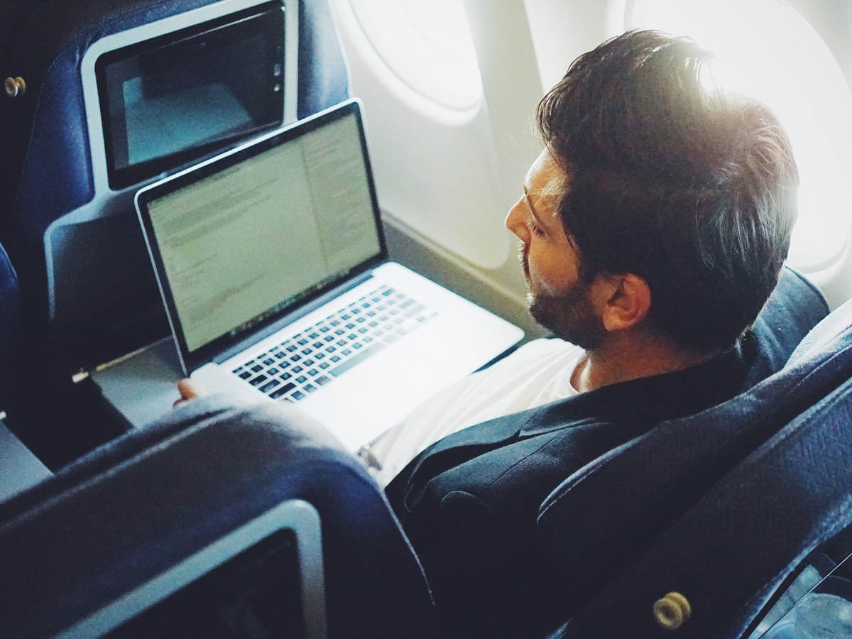 Man using a laptop on an airplane