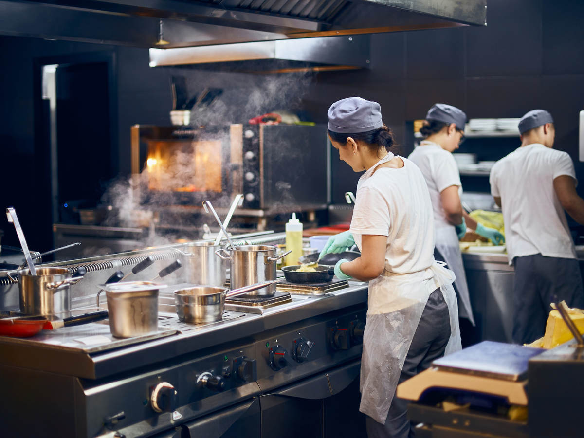 the team of cooks backs in the work in the modern kitchen, the workflow of the restaurant in the kitchen.
