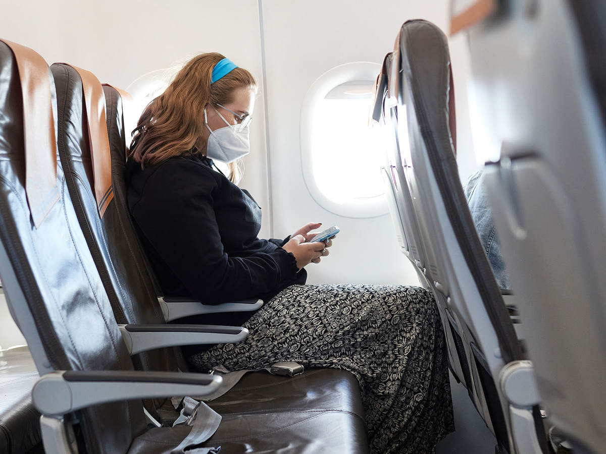 woman with cellphone on a plane that has lithium-ion battery