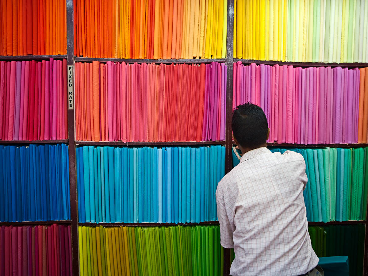 Man looking at colorful bolts of material