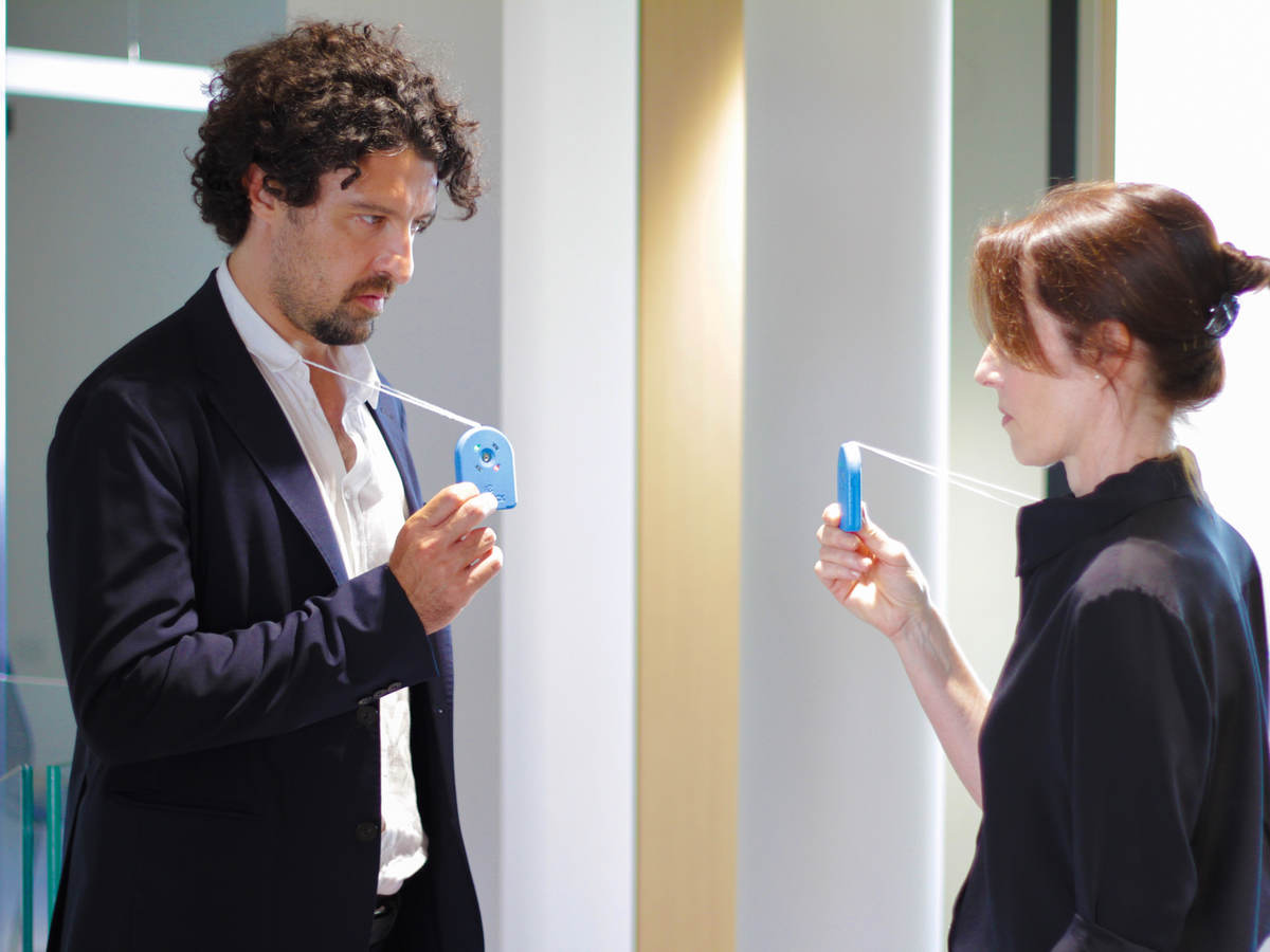 A man faces a woman with both hold an ID badge on a layard that is on their neck