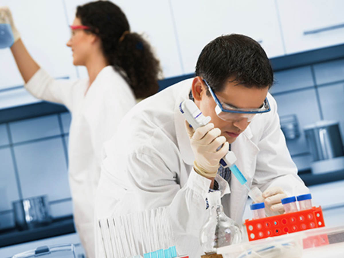 scientists in lab with orange vial container and blue liquid beaker.