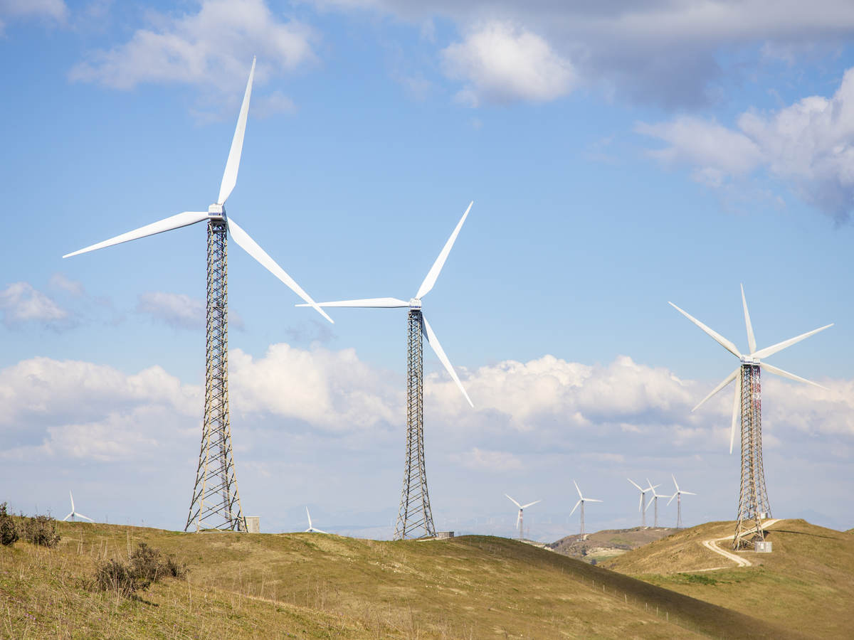 Wind turbines on a treeless hill under a blue sky with billowy clouds