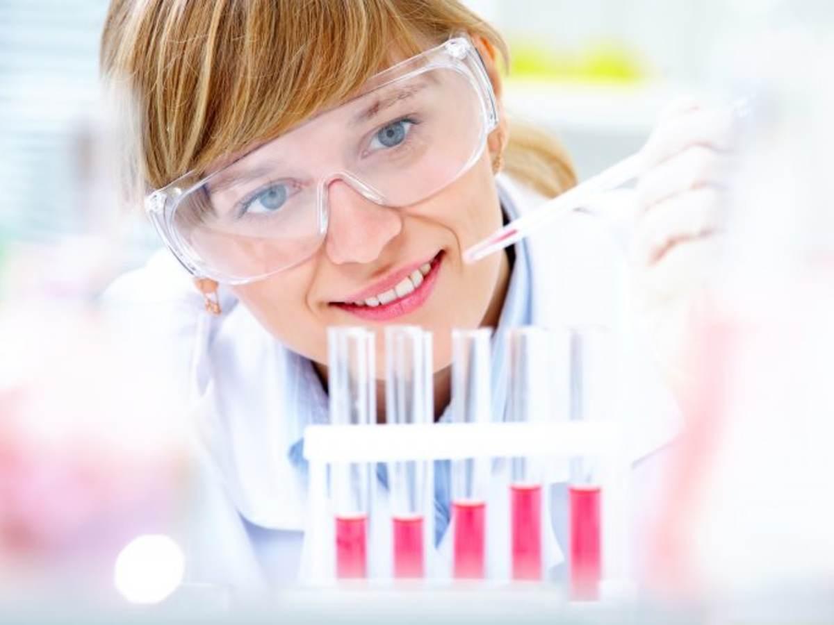 Female scientist dripping liquid into vials