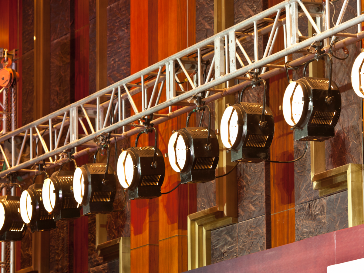Theater lights hang from backstage scaffolding, ready for the upcoming performance.