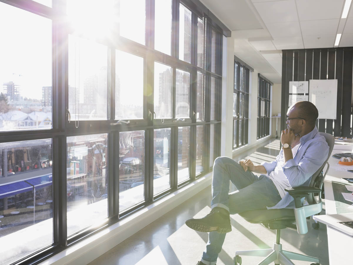 Man sitting in office looking out window.