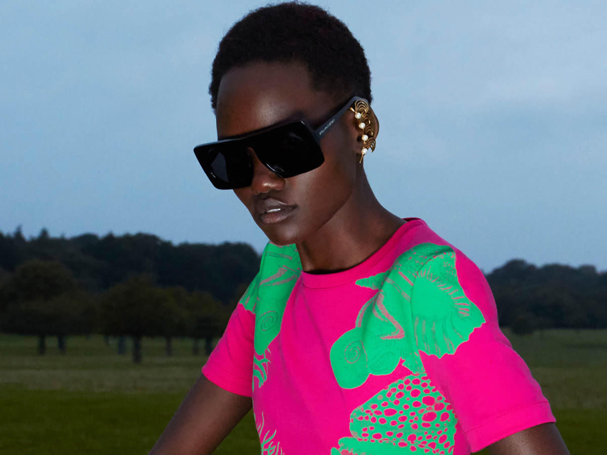 Woman wearing pink and green dress and sunglasses