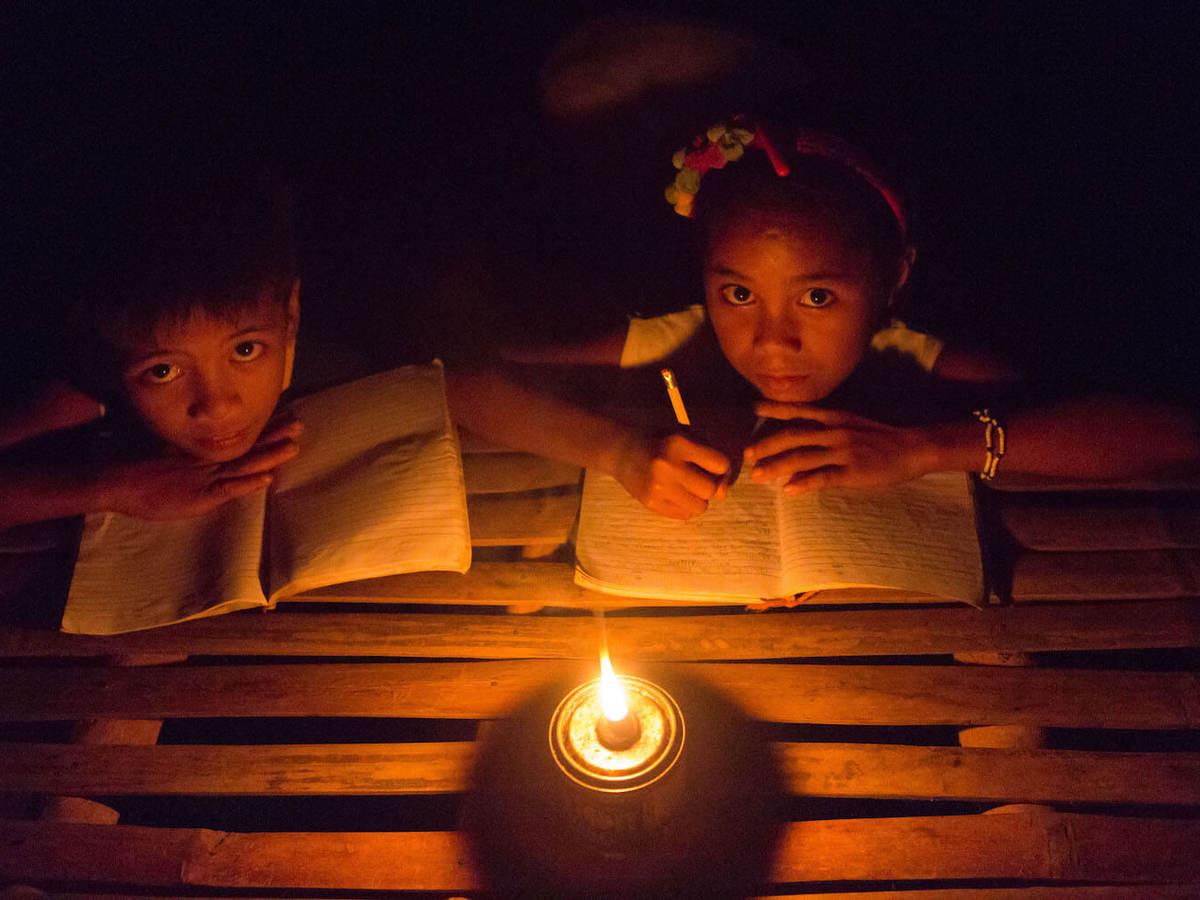 Children studying by kerosene lantern