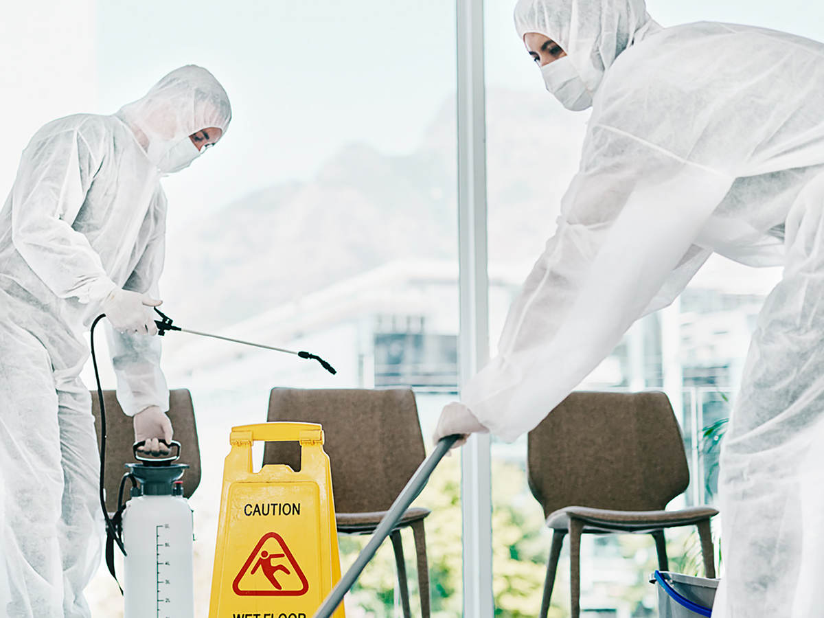 Workers wearing PPE disinfecting office
