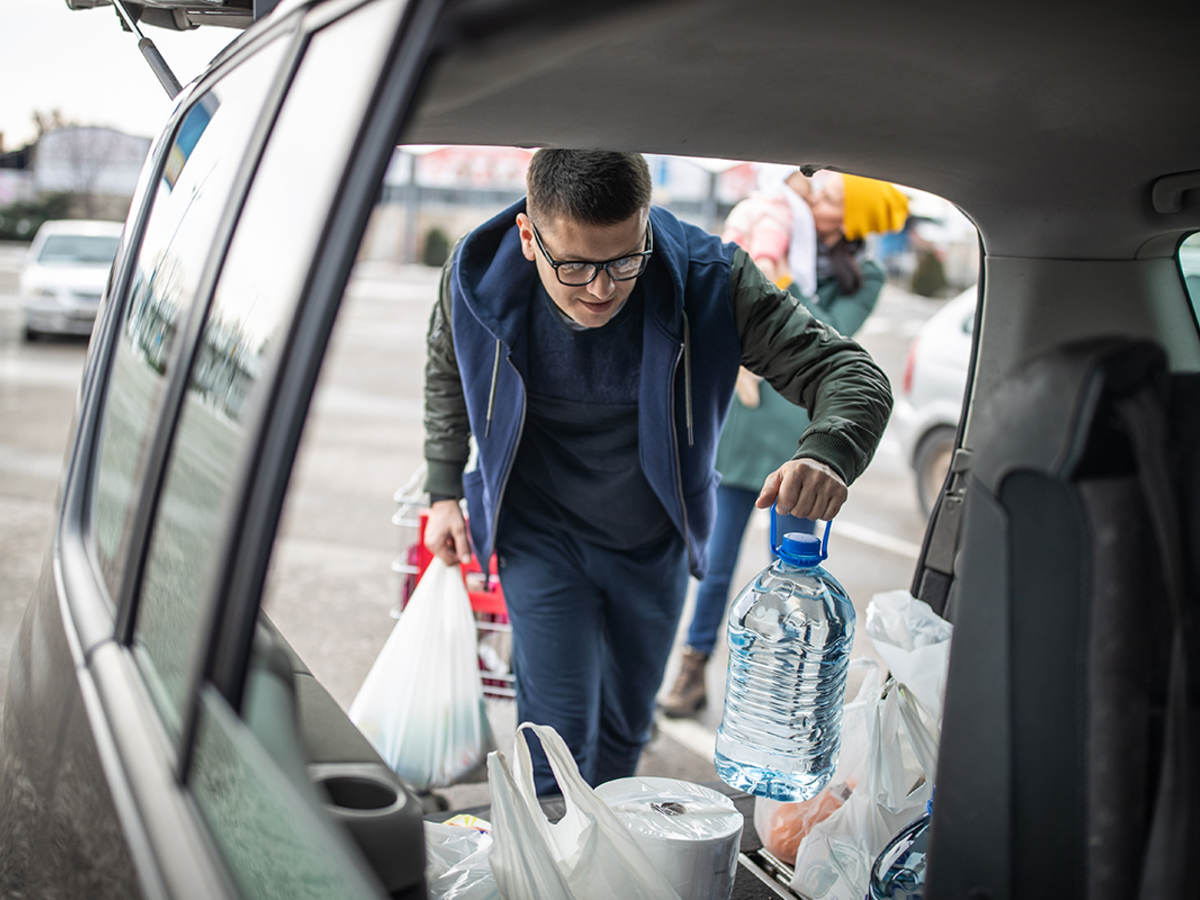 Man loading groceries into trunk
