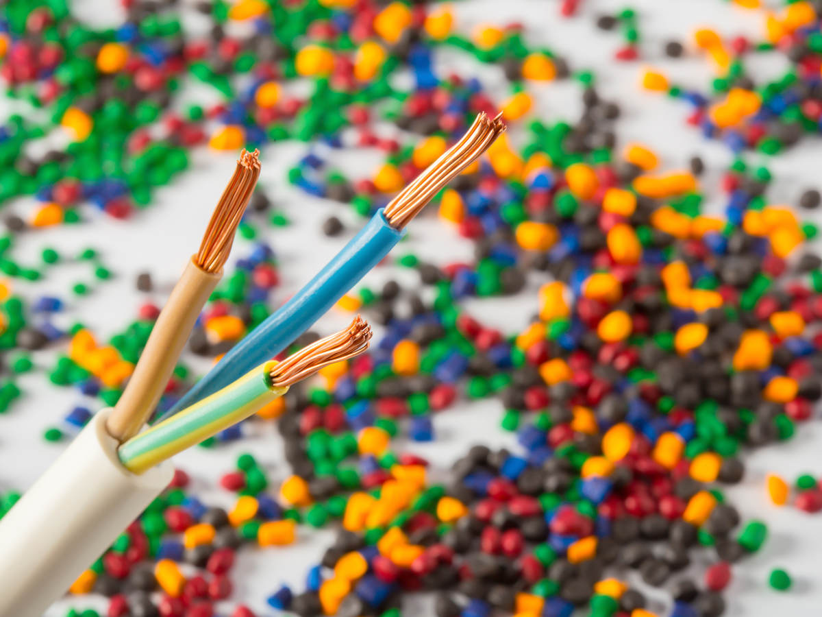 Plastic coated wire cable with plastic polymer granules in the background