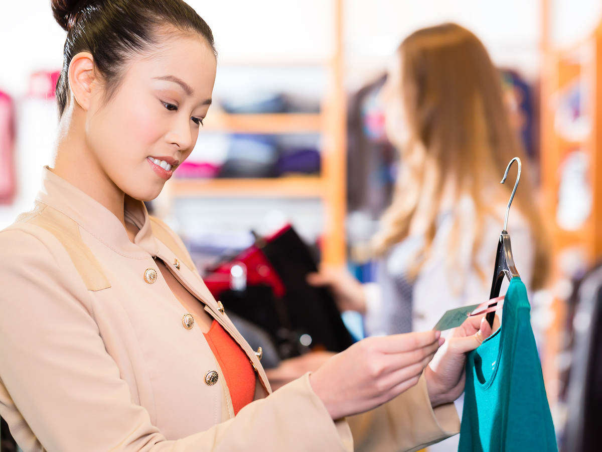 Woman checking tag on clothing in a retail shop