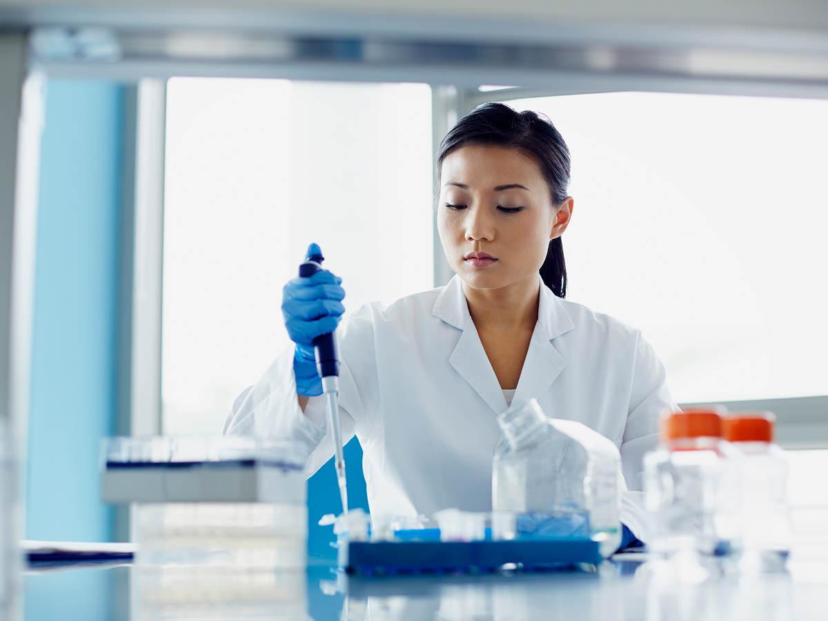 worker in laboratory using dropper