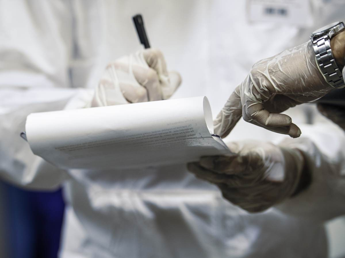 Two medical professionals' hands jotting down information on legal pad
