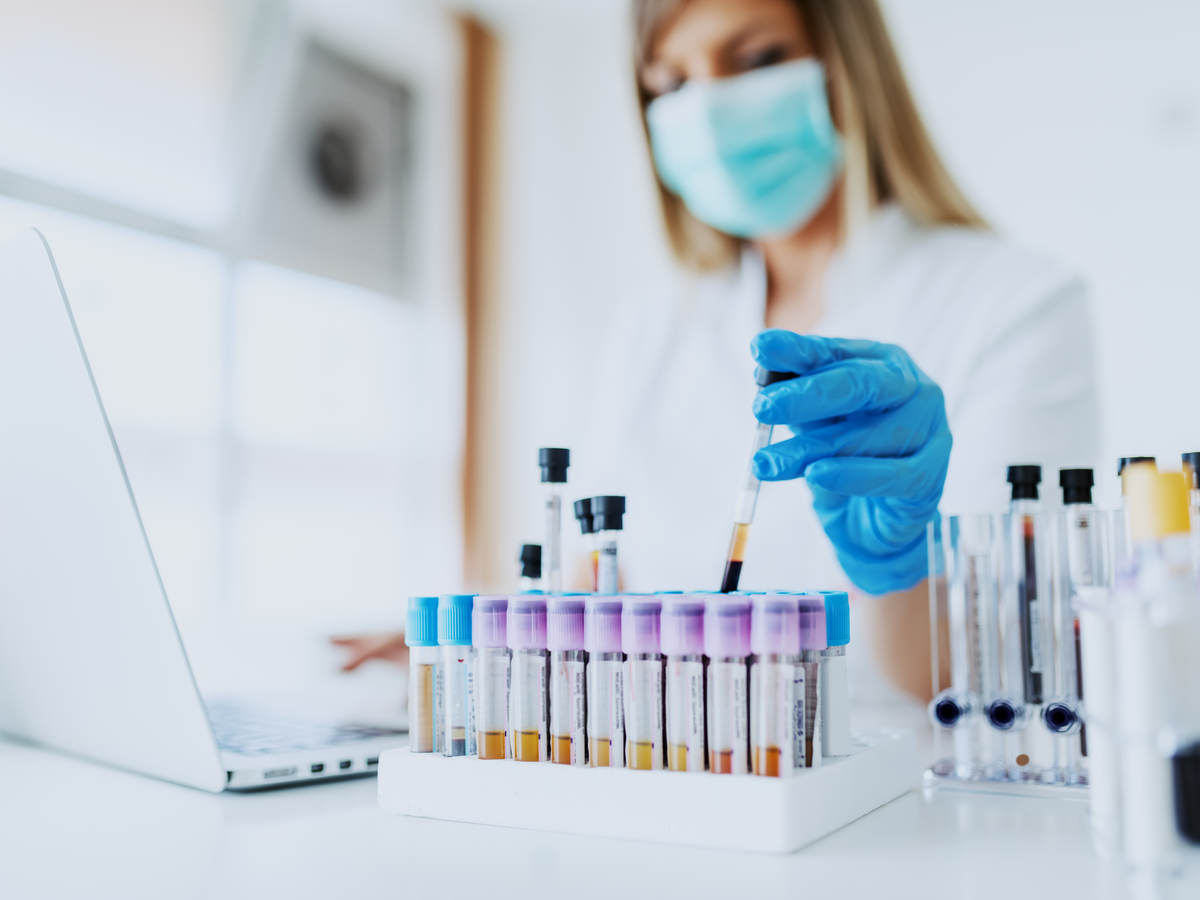 Woman wearing face mask in bright white lab observing vials while logging information on laptop