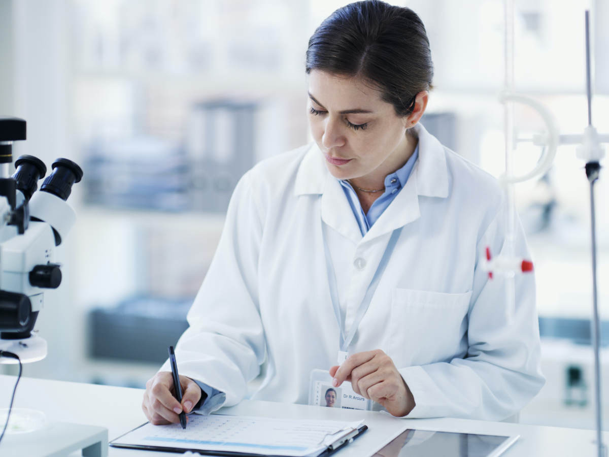Female laboratory employee at work, taking notes in a lab setting