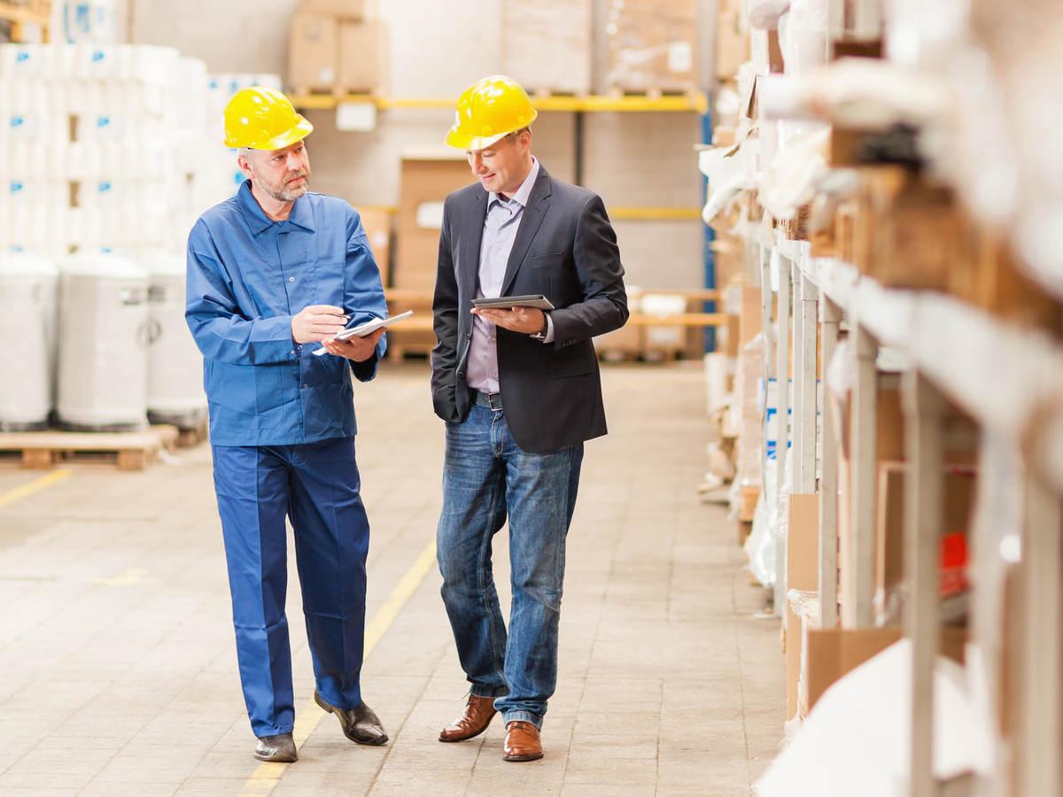 Men wearing hardhats in warehouse talking