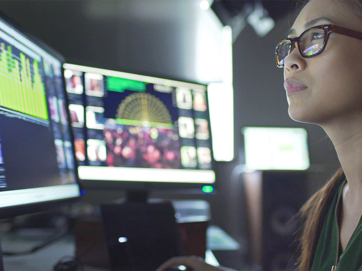Close up image of a young Asian woman with monitors
