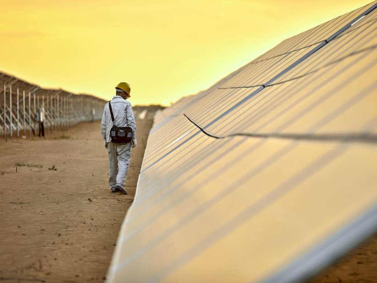 Outdoor solar pnael test facility with golden sky  and with man inspecting PV solar panels