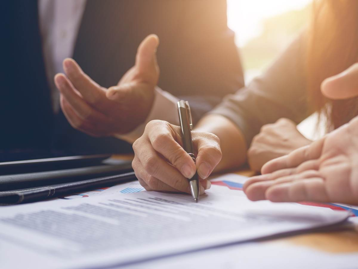 People at a desk signing a contract