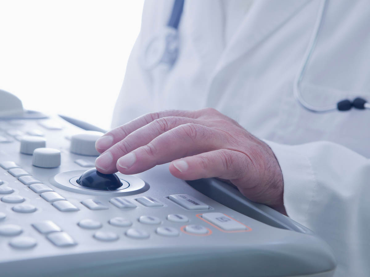 A doctor operates an ultrasound scanner