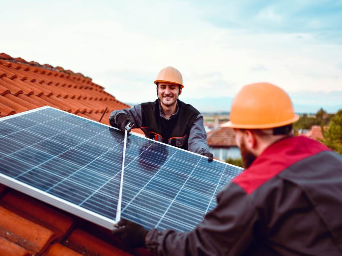 Two technicians install a solar planel on a tile rooftop