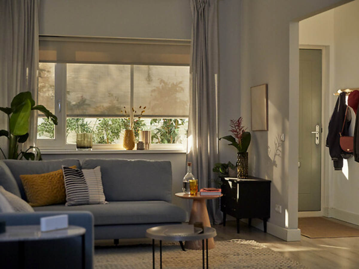 contemporary living room with smart shades, curtains and the Somfy device on an end table