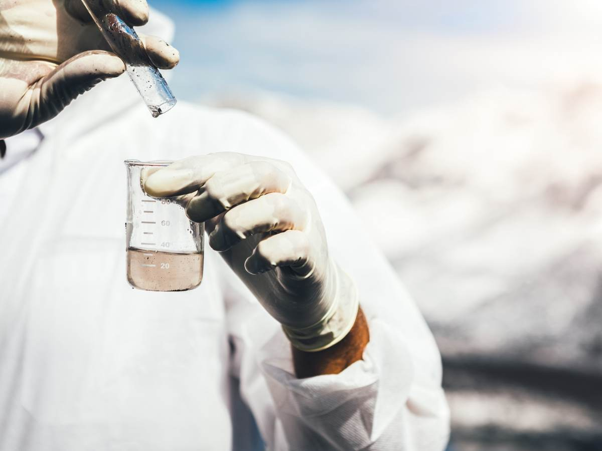 Person in protective suit examining polluted water