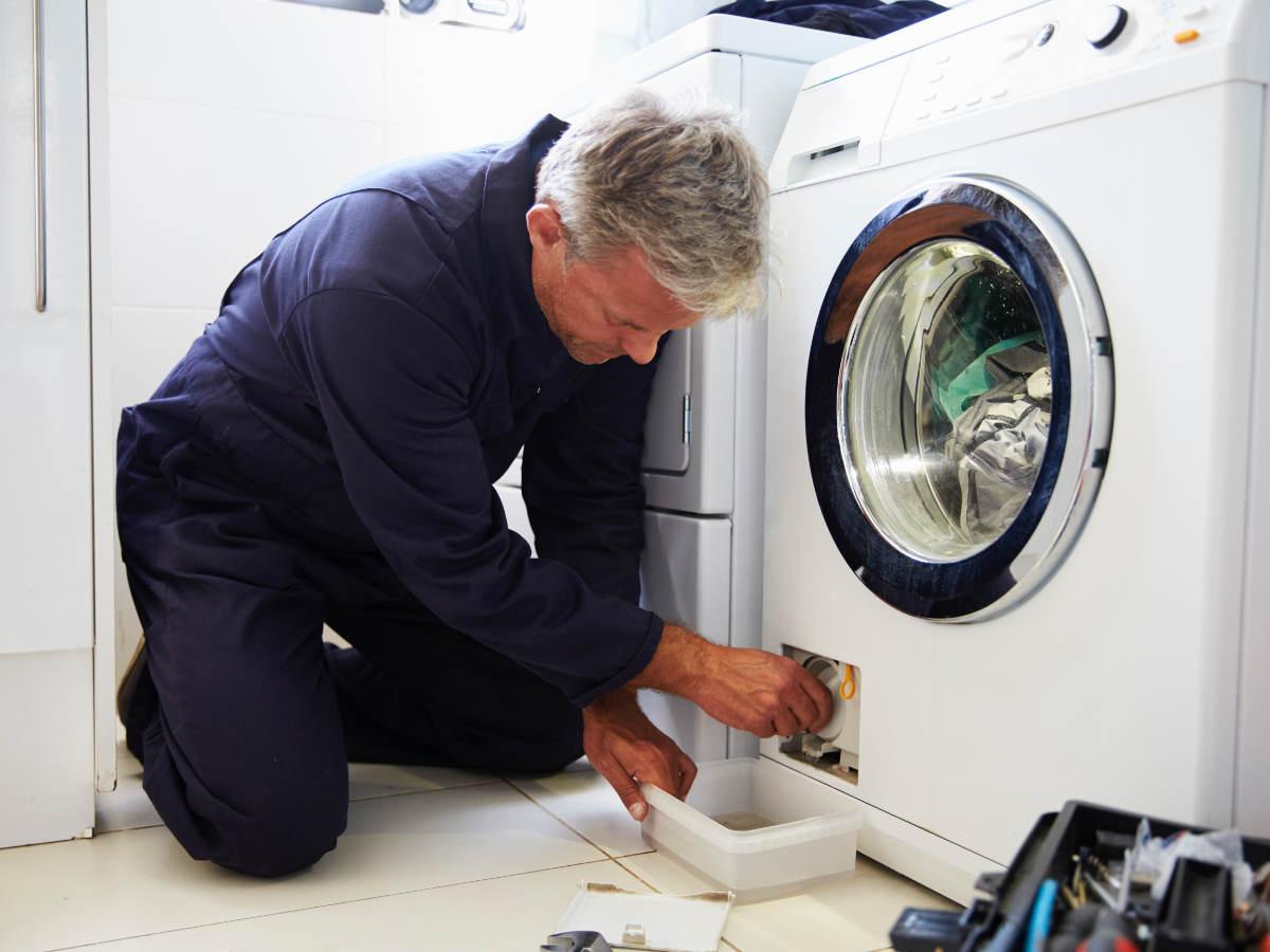 Repairman working on clothing dryer