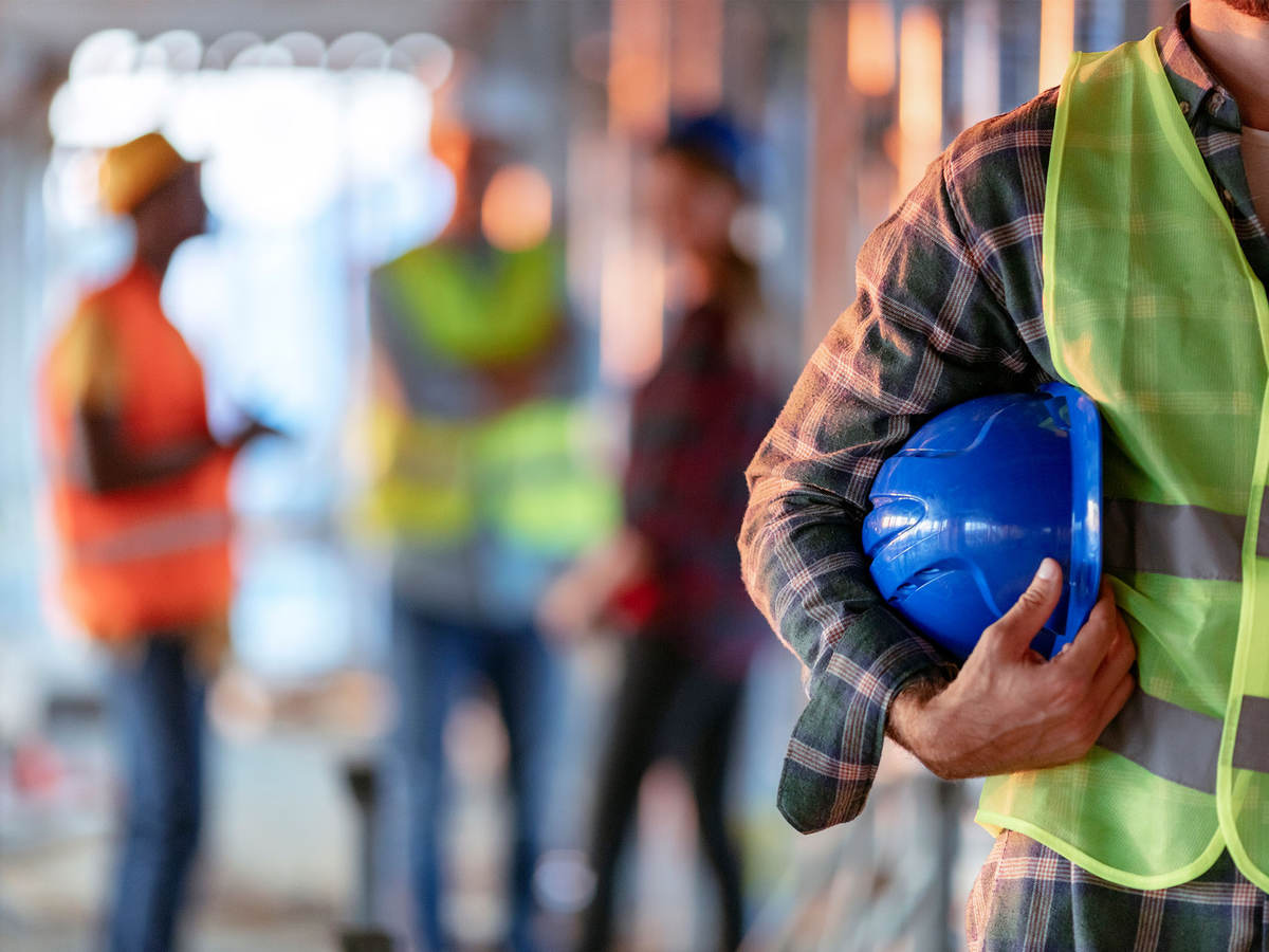 Man holding blue hard hat while on the job at warehouse