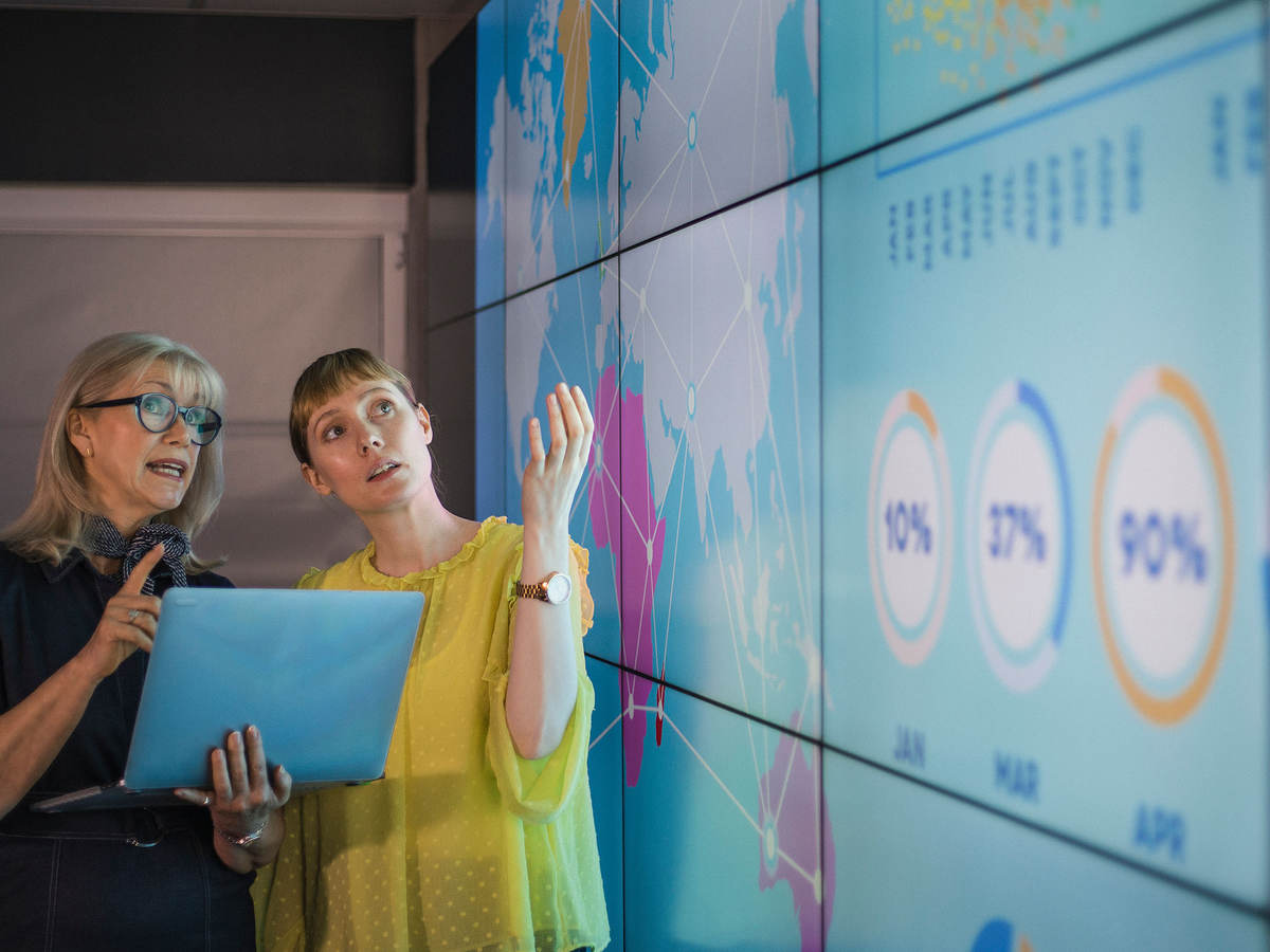 Professionals review data on a laptop and on a larger wall display