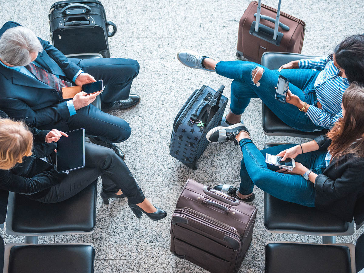 Passengers using mobile devices while waiting at an airport