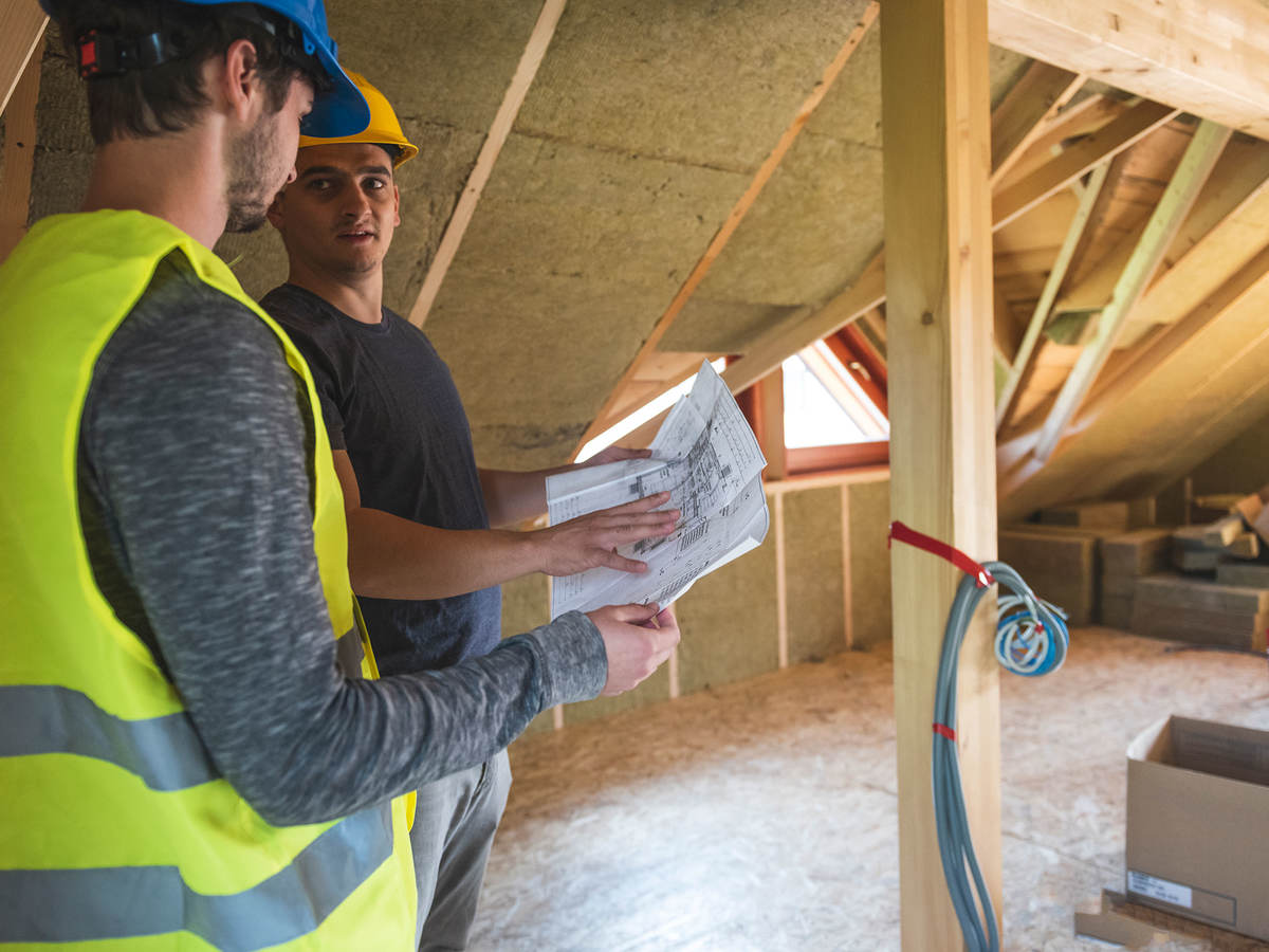 Workers discussing blueprints in an attic