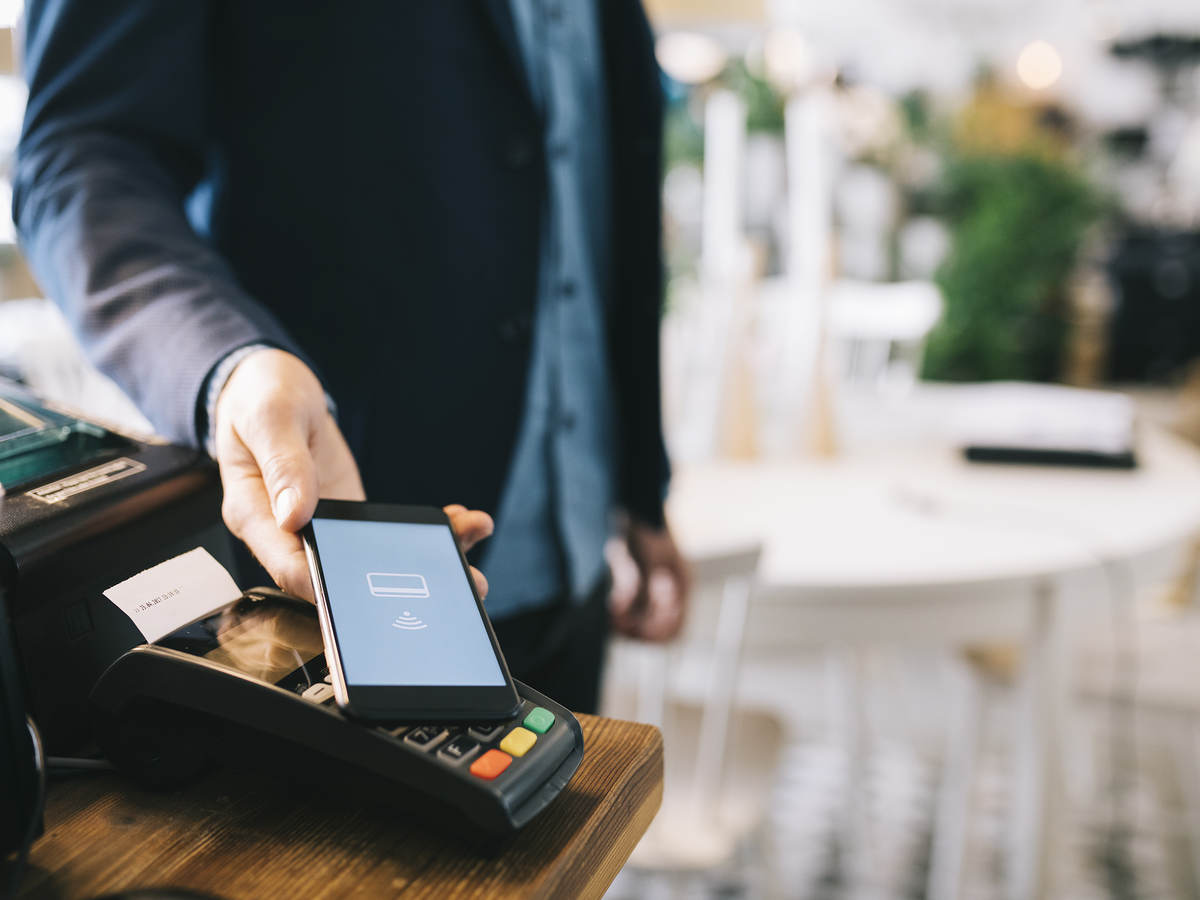 Man paying with smartphone using NFC