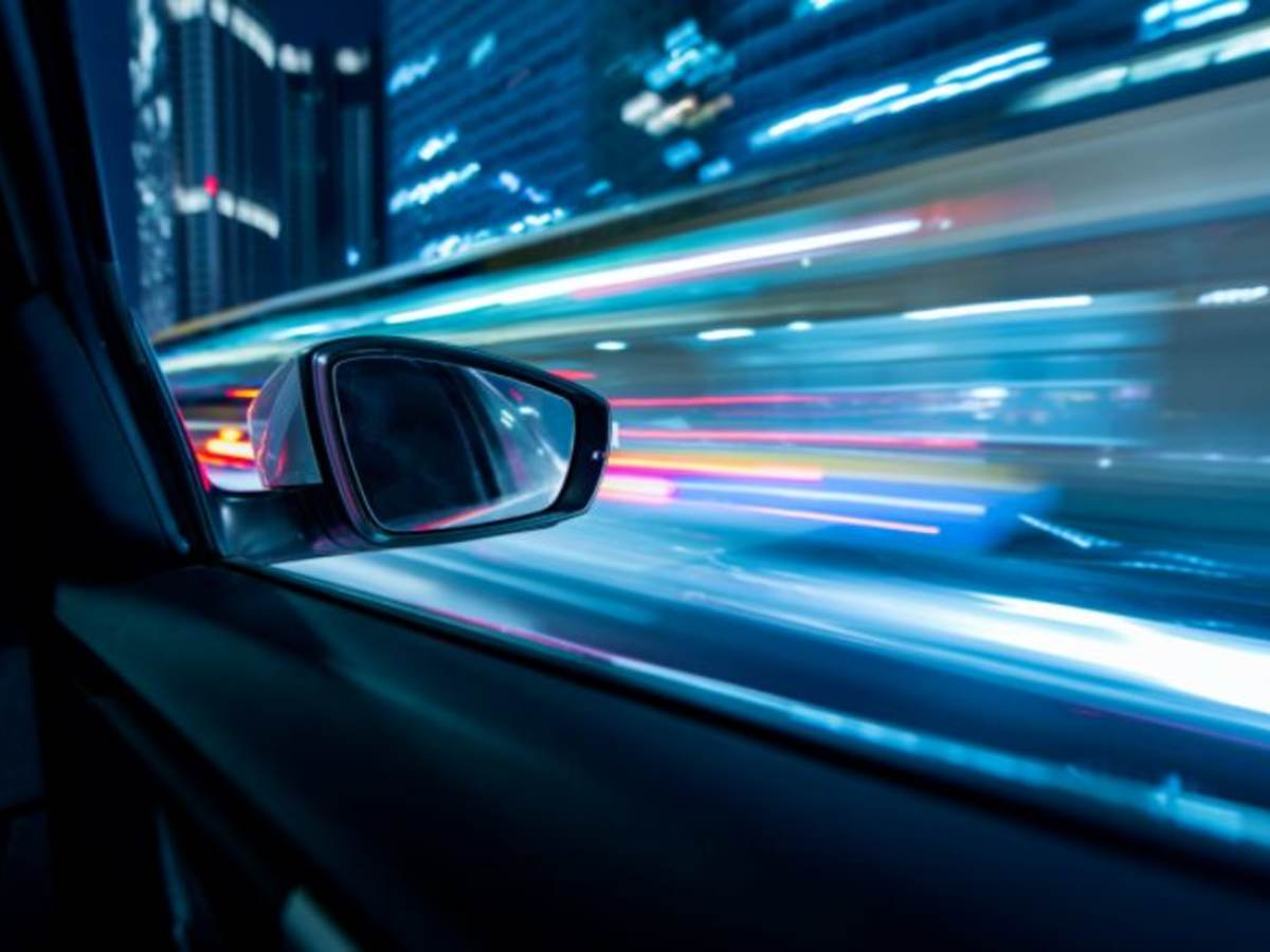 View from inside a moving car looking out of the passenger side with city lights in view