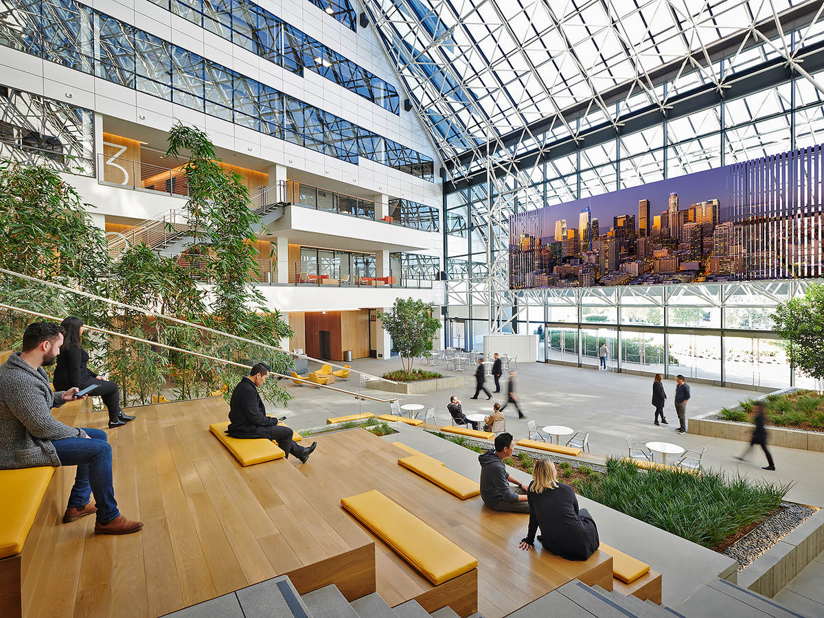 multi-storey atrium in commerical office building with people on wooden benches