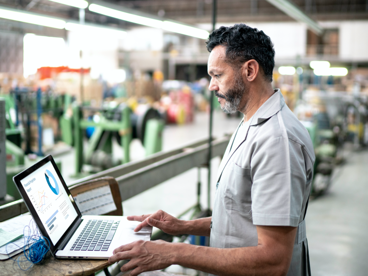 Manufacturer using a laptop on the warehouse floor